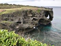 Выдающая скала и ослеплять взгляд изумрудного океана на накидке Manzamo в Японии стоковые фотографии rf