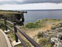 Выдающая скала и ослеплять взгляд изумрудного океана на накидке Manzamo в Японии стоковое фото rf
