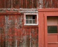 Выдержанная красная краска и сломленные окна общее место на амбаре стоковые фото