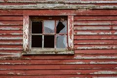 Выдержанная красная краска и сломленные окна общее место на амбаре стоковые изображения