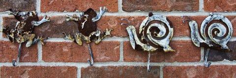 Выдержанные крюки лягушки и улитки прикрепленные к кирпичной стене стоковые фотографии rf