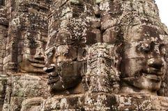 Выдержанные, покрытые Лишайник каменные главные статуи в Angkor Wat, Siem Reap, Камбодже, Индо-Китае, Азии - стороне дальше в цве стоковое фото rf