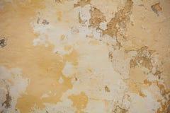 Выдержанный желтый цвет покрасил частично увяданную предпосылку стены, Стоковые Фотографии RF