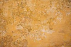Выдержанный желтый цвет покрасил частично увяданную предпосылку стены, Стоковая Фотография