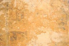 Выдержанный желтый цвет покрасил частично увяданную предпосылку стены, Стоковое Фото