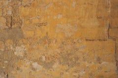Выдержанный желтый цвет покрасил частично увяданную предпосылку стены, Стоковая Фотография RF