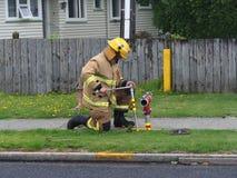 Вызывайтесь добровольцем пожарный рукав первого ответчика соединяясь к водопроводу Стоковые Фотографии RF