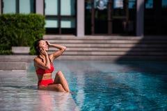 Вызывать всех ее друзей для того чтобы соединить Портрет счастливой молодой женщины сидя бассейном говоря на ее смеяться над теле Стоковая Фотография RF