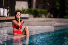 Вызывать всех ее друзей для того чтобы соединить Портрет счастливой молодой женщины сидя бассейном говоря на ее смеяться над теле Стоковое фото RF
