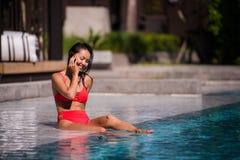 Вызывать всех ее друзей для того чтобы соединить Портрет счастливой молодой женщины сидя бассейном говоря на ее смеяться над теле Стоковые Фотографии RF
