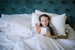 Вызывать девушки видео- на мобильном телефоне в спальне Стоковое Изображение