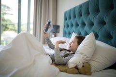 Вызывать девушки видео- на мобильном телефоне в спальне Стоковые Фото
