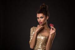 Выигрывать женщины - молодая женщина в первоклассном платье золота держа 2 красных обломока, покер тузов чешет комбинация Стоковые Фото