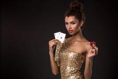 Выигрывать женщины - молодая женщина в первоклассном платье золота держа 2 туза и 2 красных обломока, покер тузов чешет комбинаци Стоковое Фото