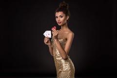 Выигрывать женщины - молодая женщина в первоклассном платье золота держа 2 туза и 2 красных обломока, покер тузов чешет комбинаци Стоковое Изображение RF