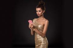 Выигрывать женщины - молодая женщина в первоклассном платье золота держа 2 карточки, покер тузов чешет комбинация взволнованности Стоковые Изображения