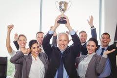 Выигрывая дело объединяется в команду с исполнительным держа трофеем стоковое изображение rf
