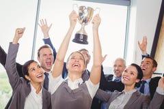 Выигрывая дело объединяется в команду с исполнительным держа трофеем стоковые фотографии rf