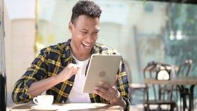 Выигрывая молодой африканский человек возбужденный для успеха на планшете, на открытом воздухе кафе сток-видео