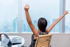 Выигрывая оружия работницы офиса вверх в успехе стоковая фотография