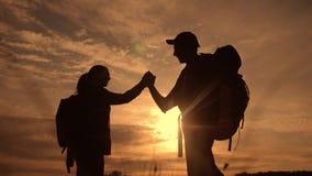 Выигрыш концепции путешествием дела сыгранности Туристы человек команды и успех рук встряхивания помощи силуэта захода солнца обр видеоматериал