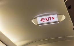 Выйдите знак на накладных расходах в строке i аварийного выхода самолета пассажира Стоковая Фотография RF