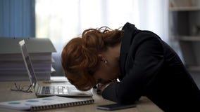 Вымотанная женщина лежа на столе офиса, работая крепко на проекте, давление крайнего срока стоковые фотографии rf