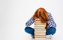 Вымотанная женщина положила голову на стог книг и спать Стоковое фото RF