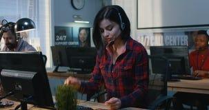 Вымотанная женщина работая в центре поддержки