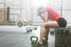 Вымотанная женщина сидя на автошине в спортзале crossfit Стоковое Изображение RF
