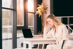 Вымотанная коммерсантка в костюме сидя на таблице в офисе Стоковая Фотография