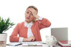 Вымотанная коммерсантка работая на столе офиса имеет головную боль Стоковая Фотография