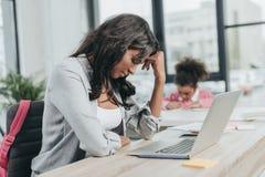 Вымотанная коммерсантка сидя на рабочем месте перед компьтер-книжкой Стоковые Фото