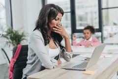 Вымотанная коммерсантка сидя на рабочем месте перед компьтер-книжкой Стоковое Фото