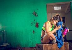 Вымотанная питьевая вода девушки спортзала Стоковая Фотография RF