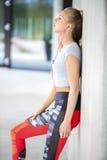 Вымотанная подходящая женщина в склонности Sportswear на стене Стоковые Фотографии RF