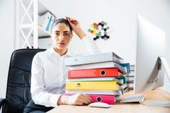Вымотанная утомленная коммерсантка сидя на столе офиса Стоковые Фотографии RF