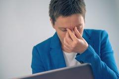 Вымотанное дополнительное время коммерсантки работая на comput компьтер-книжки офиса Стоковые Изображения RF