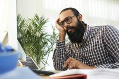 Вымотанный бизнесмен работая на офисе стоковое изображение