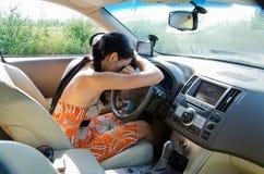Вымотанный водитель отдыхая на рулевом колесе стоковое фото