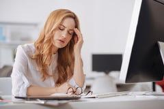 Вымотанный менеджер страдая от хронических ежедневных головных болей в офисе Стоковое фото RF