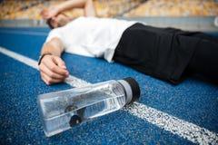 Вымотанный молодой спортсмен лежа на беговой дорожке стоковые изображения rf