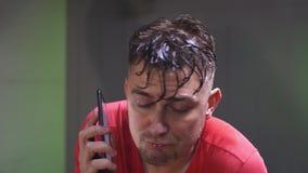 Вымотанный потеть красный t-shirted человек делать cardio и говорить по телефону видеоматериал