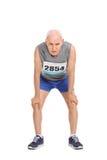 Вымотанный старший бегун на белой предпосылке Стоковое фото RF