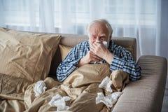 Вымотанный старый мужчина болен в спальне стоковое изображение