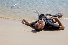 Вымотанный человек лежа на пляже моря Стоковые Изображения RF