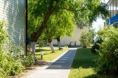 Вымощенный переулок с кустами, деревьями, фонариками Стоковое Фото