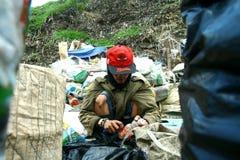 Выноситель сортируя через погань на месте сброса в Маниле, Филиппинах для того чтобы искать recyclable вещи стоковое фото