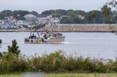 Выносливость рыбацкой лодки с барьером урагана New Bedford в bac стоковое изображение rf