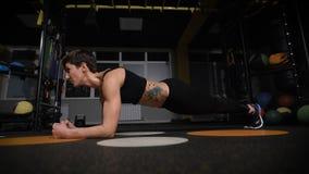 Выносливость тренировки фитнес, спорт, тренировка, спортзал и концепция образа жизни - протягивать молодую женщину с наушниками в сток-видео